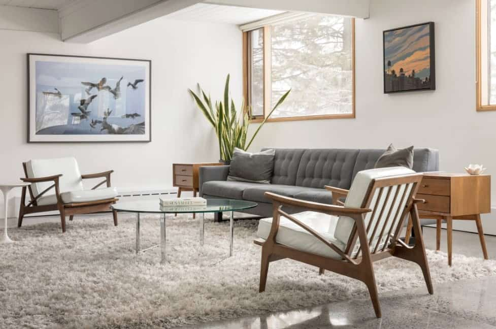 Mid-century modern living room accented with lovely wall arts mounted on the white walls. It has a gray tufted sectional that sits in between end tables accompanied by white cushioned armchairs and a round glass top coffee table on a shaggy rug.