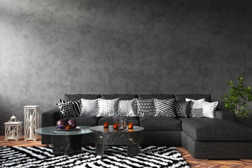 Living room with a black L-shaped sectional sofa accented with various styled throw pillows and patterned rug over herringbone wood flooring.