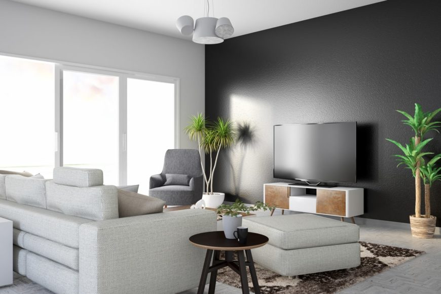 Fresh living room features a gray sofa with an ottoman facing the television above a wooden stand. It has indoor plants on the sides creating a tropical feel.