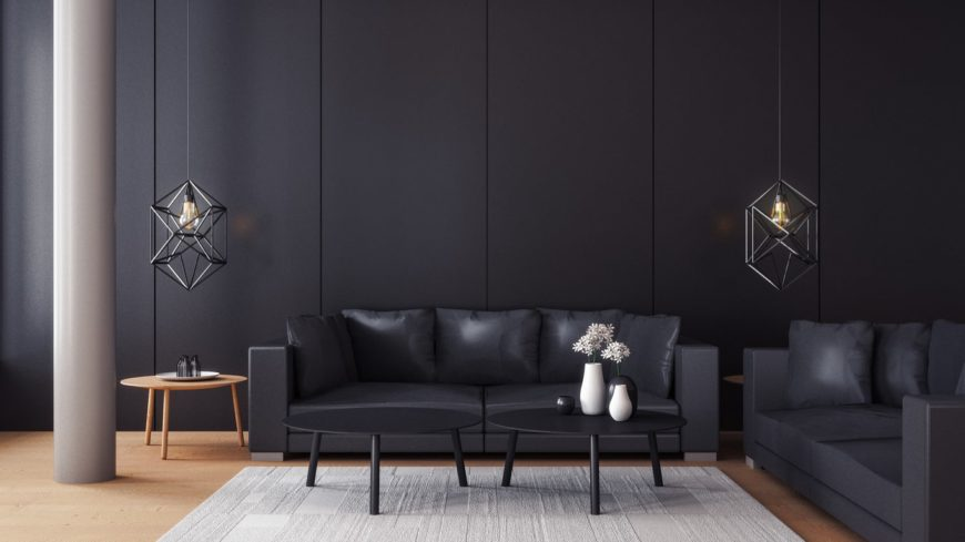 Black adjacent sofas sit on hardwood flooring topped with a gray rug in this living room. It is lighted by a pair of industrial pendants.