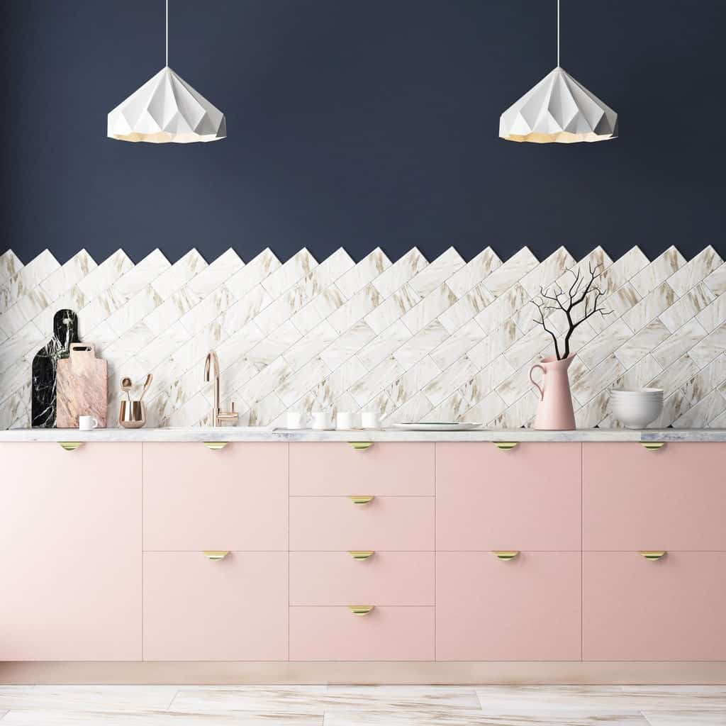This kitchen boasts a striking backsplash illuminated by lovely pendant lights. It includes a blush pink cabinetry contrasted by the navy blue wall.
