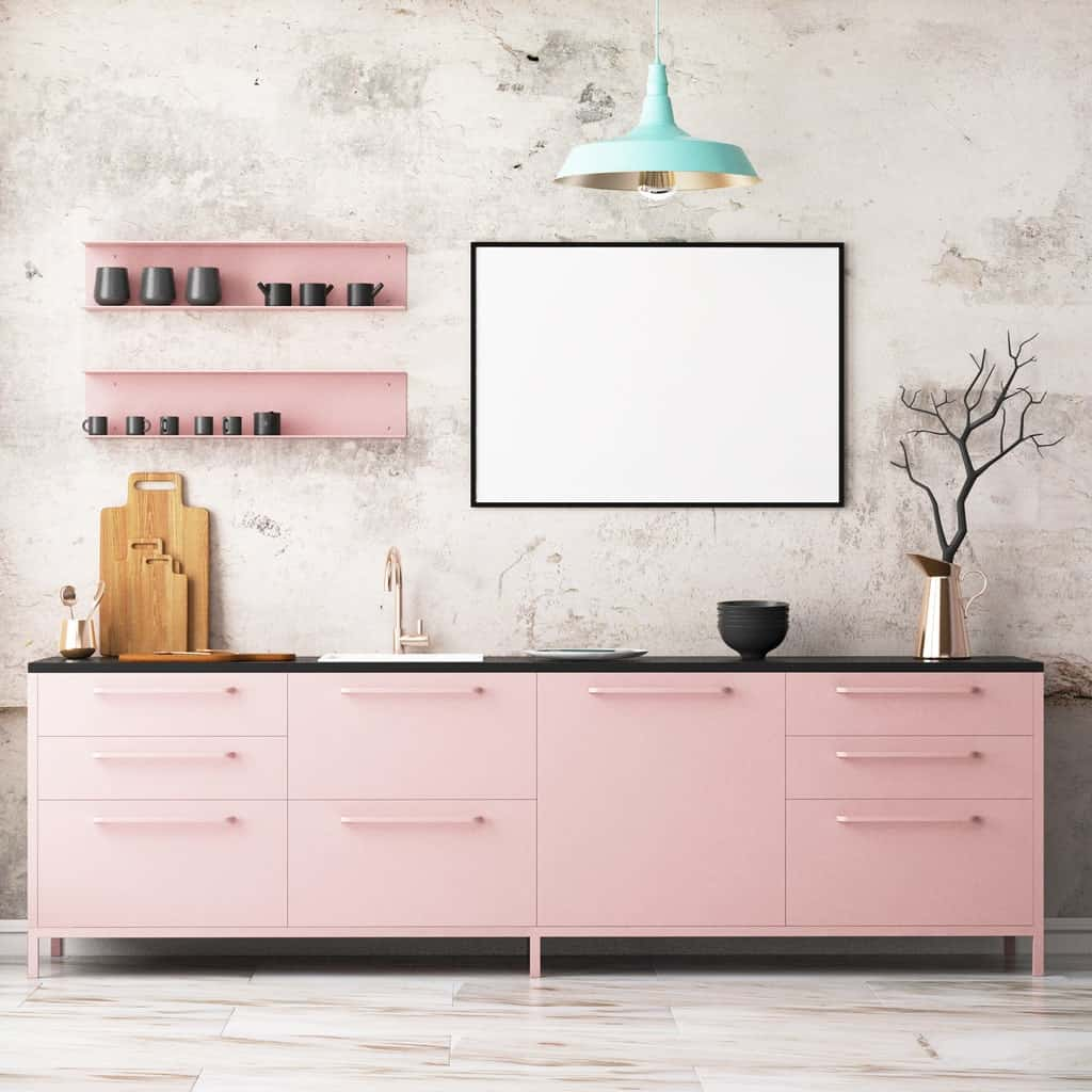 Attractive kitchen with light pink cabinetry topped with a black granite counter. It has floating shelves next to a whiteboard lighted by a mint green pendant.