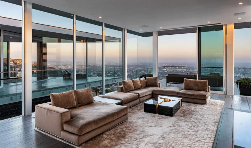 This bright modern living room is highlighted by the amazing city skyline view that is presented by the surrounding glass walls. These also bring in an abundance of natural lighting that brightens the large brown L-shaped couch that matches with the brown area rug.