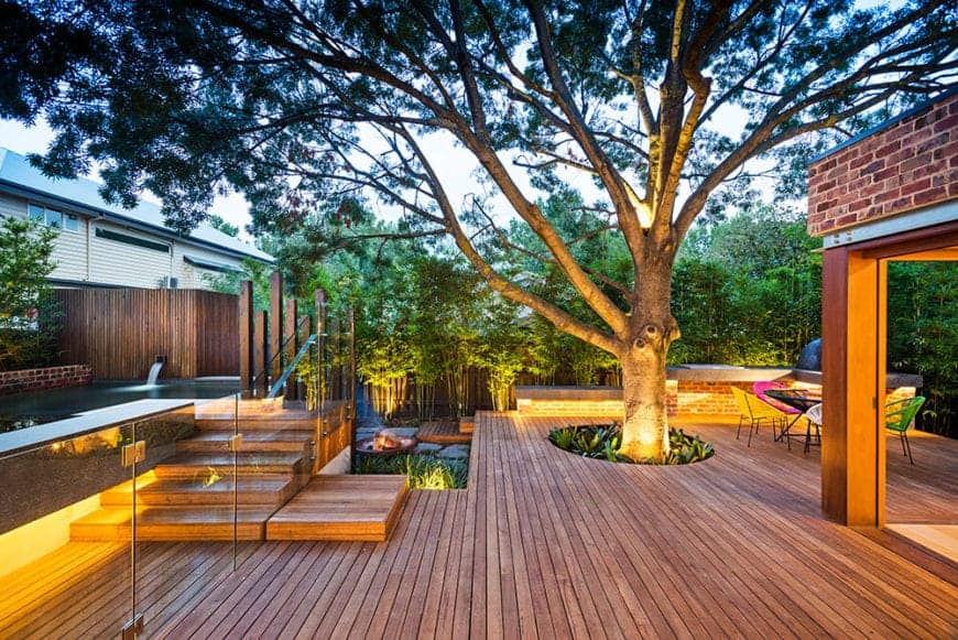 Wooden deck with a huge beautiful tree provides a statement that really catches the eye. Beside it is a wooden stairs with glass railing that leads to the pool.