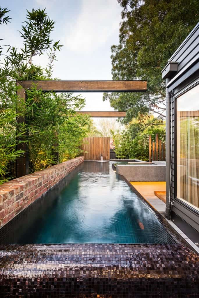 Secluded pool with mosaic tiles, brick walls, wood accents that enhances its beauty and bamboo plants that serve as its fence.