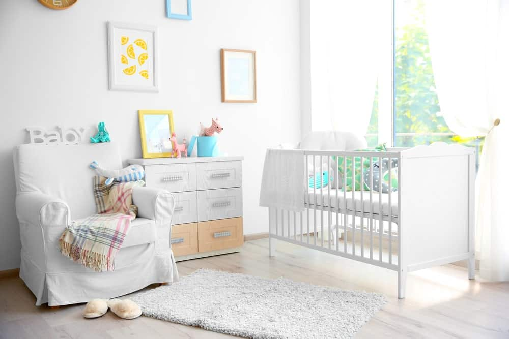 White nursery interior with wall arts.
