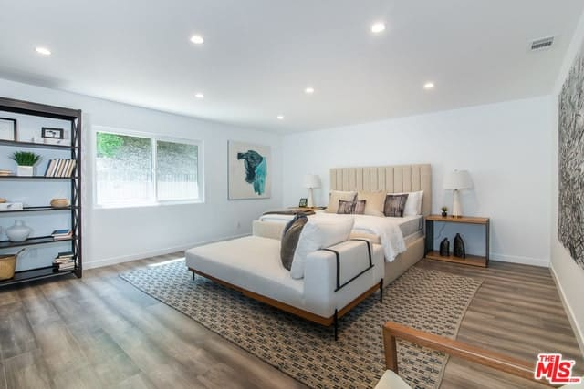This primary bedroom features a taupe bed that's paired with a white sofa bench over a rug. It is illuminated with recessed lighting beautifully scattered from the white ceiling.