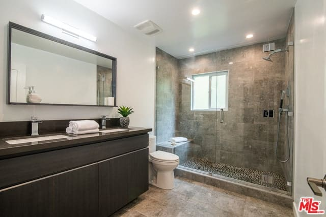 Master bathroom with a brick walk-in shower area and a glass enclosure. It has a dark wood dual sink vanity with mirror and wall lamp.