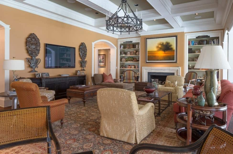 Warm craftsman style living room with antique decor pieces, classic printed rug, a variety of mid-century armchairs, and an antique style chandelier.