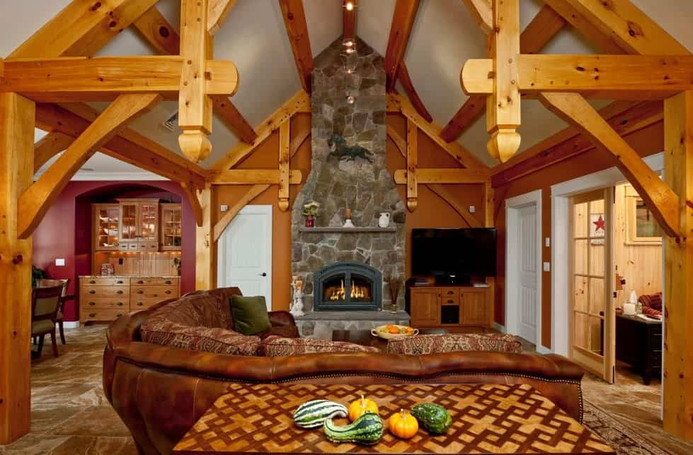 Craftsman style living room with visible wooden beams, brown L-shaped leather sofa,  a fireplace,and rustic wooden cabinets.