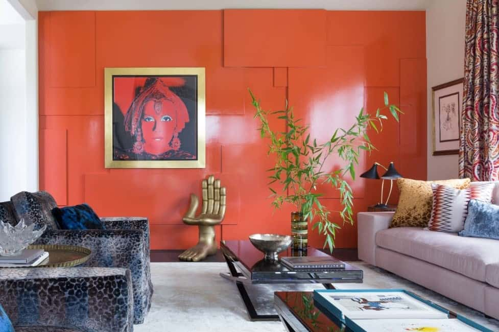Decorative living room with an orange artistic wall, light gray sofa, printed pillows, leopard print cozy armchairs, and a rectangular center table.