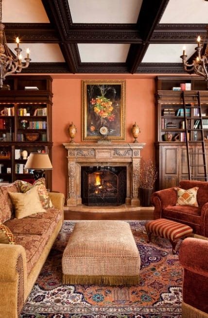 Traditional orange themed living room with coffered ceiling, Victorian style chandeliers, traditional rug, upholstered center table, antique furniture, and a cozy sofa.