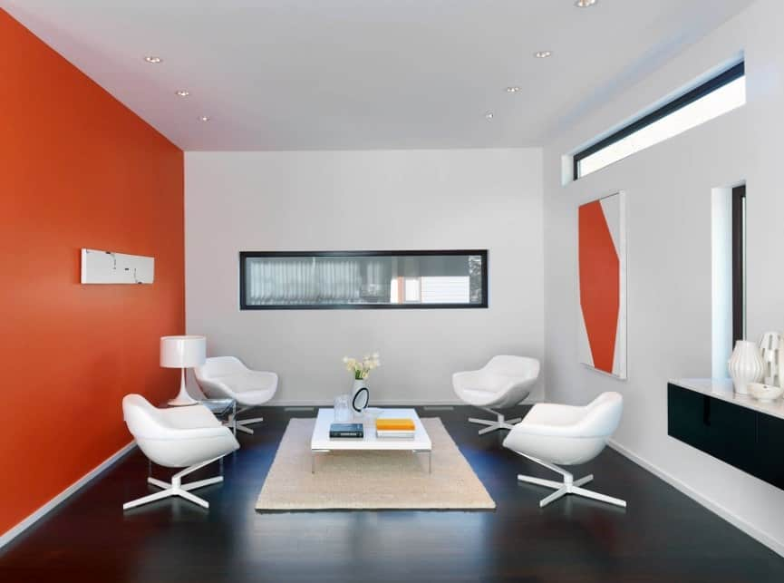 Modern living room with orange walls, black flooring, four white modern armchairs, white square center table, and recessed lights.