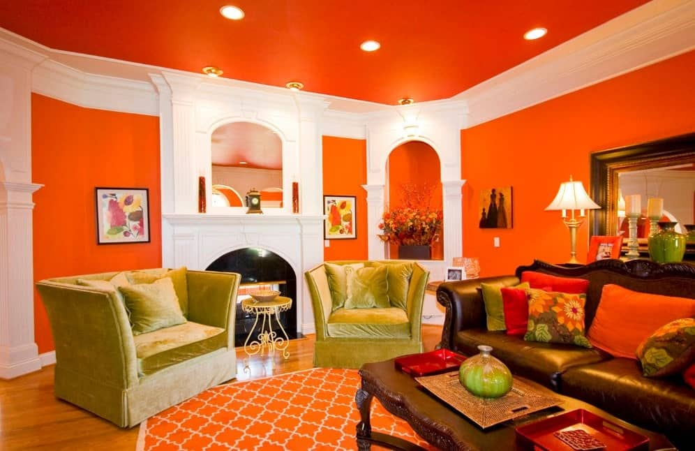 Vibrant living room with orange walls, yellow-green velvet armchairs, brown traditional sofa, antique brown center table, and hardwood floors.