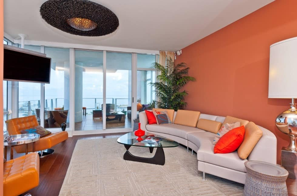 A muted toned orange living room with white accents that opens to a balcony. The modern and hip sofa and table, warm-toned wooden floors and grey rug adds to the room's character.