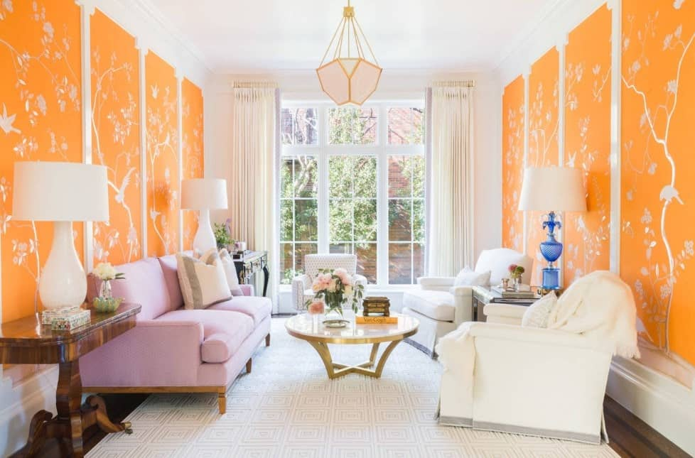 Bright and chic living room with floral printed orange walls, pastel pink sofa, two white cozy armchairs, gold and round center table, huge windows, and a stylish pendant light.