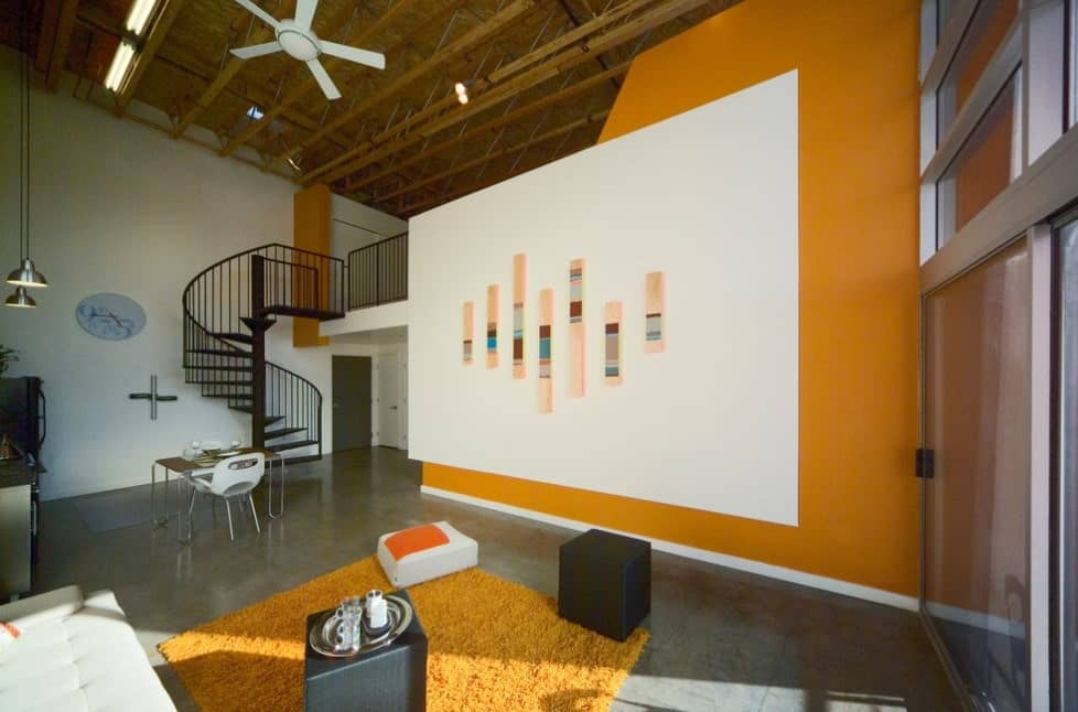 This modern living room features orange accented walls, slate gray bare floors that contrast with the orange rug, black and white furniture, predominantly white mural, metal spiral staircase, pendant lights, and exposed beams.