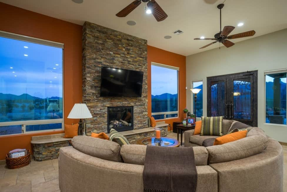 Modern media and family living room with orange and gray matte walls, gray round sofa set with matching throw pillows, stone tiled floors, and a fireplace with the textured surface of travertine ledge stone.