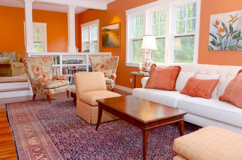 This transitional persimmon orange sunken living room with white accents combines the elegance of the Chesterfield sofa with red and white throw pillows, highback chairs with orange and blue embroidery, tan and orange seats, antique oriental rug and lamp, serene paintings, hardwood floors, and white painted windows.
