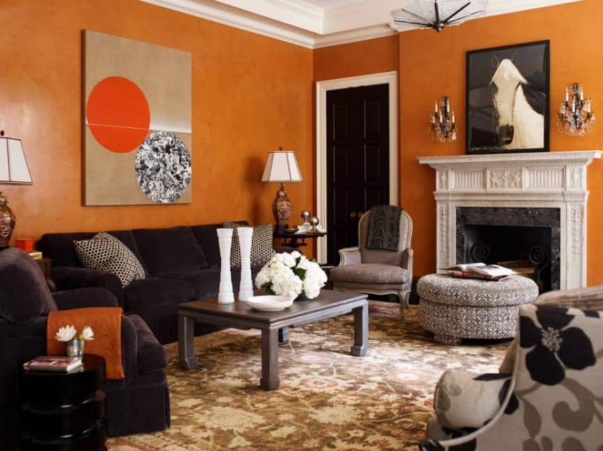 This contemporary living room has walls with combined Venetian plaster and custom made orange paint that adds to its depth and texture. The combined black, white and gray accents from the sofa, fireplace, round and square table, lamps, vases, paintings, candelabra, and carpet adds character to the room.