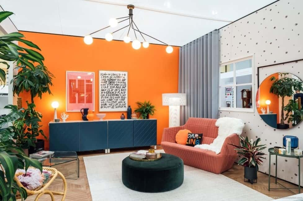 This contemporary living room does away with neutral palettes and injects a sense of fun by using vibrant contrasting colors of orange, black, terra cotta, green, pink and grey. As well as adding patterns which are not usually lumped in together like diagonals, uneven dots, and herringbone ties the room together.