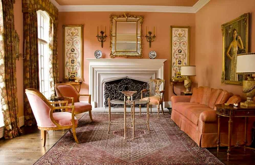 Crafty orange living room with orange walls, cozy orange sofa, chic upholstered orange armchairs, a fireplace, and antique decor pieces.