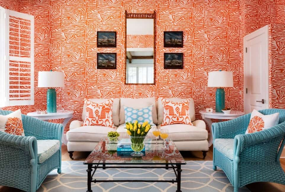 Cheerful living room in vibrantly printed walls, cozy beige sofa, two pastel blue rattan armchairs, square glass center table, and a printed powder blue rug.