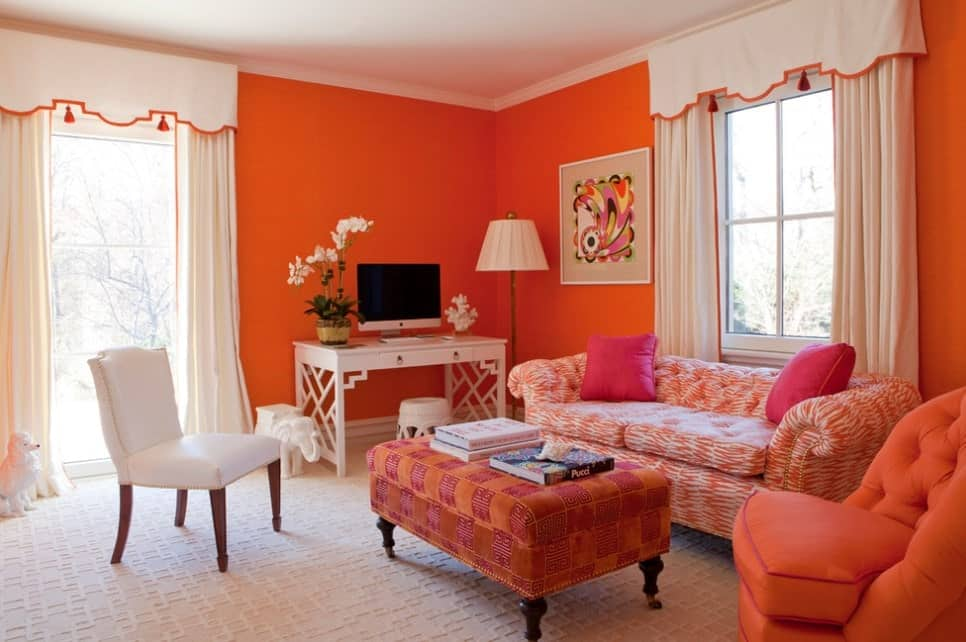 Inviting living room with orange walls, printed orange sofa, stylish textured white carpet, upholstered orange center table, with a mini office.