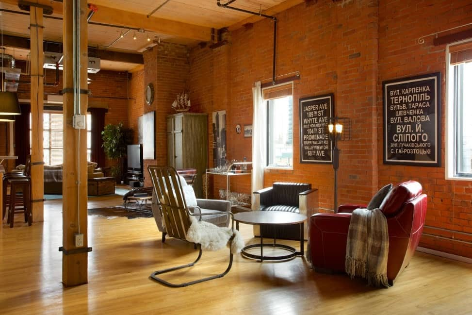 Brick walled living room with hardwood floors, leather arm chairs, round wooden table, and a floor lamp.