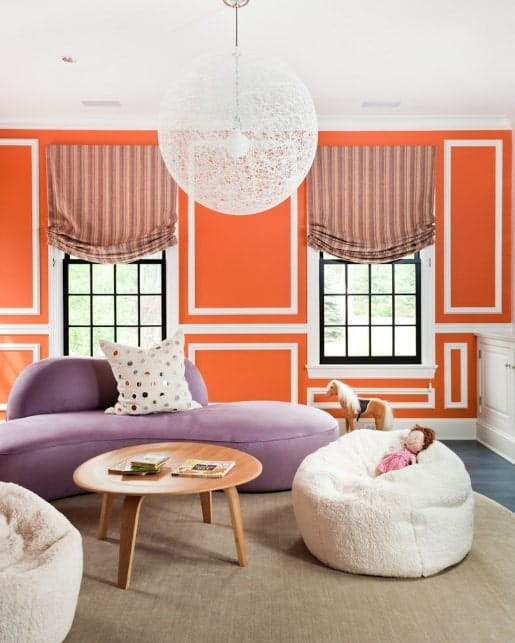 Orange living room with pastel purple sofa, fluffy white beanbags, round wooden center table. and decorative pendant light.