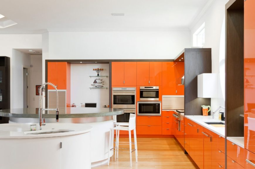A wide modern style kitchen with shiny orange cabinets, stainless appliances, and two round islands.