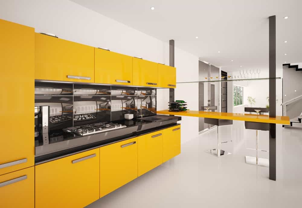Modern style wall kitchen with yellowish orange cabinets, a breakfast island, and clean white floors.