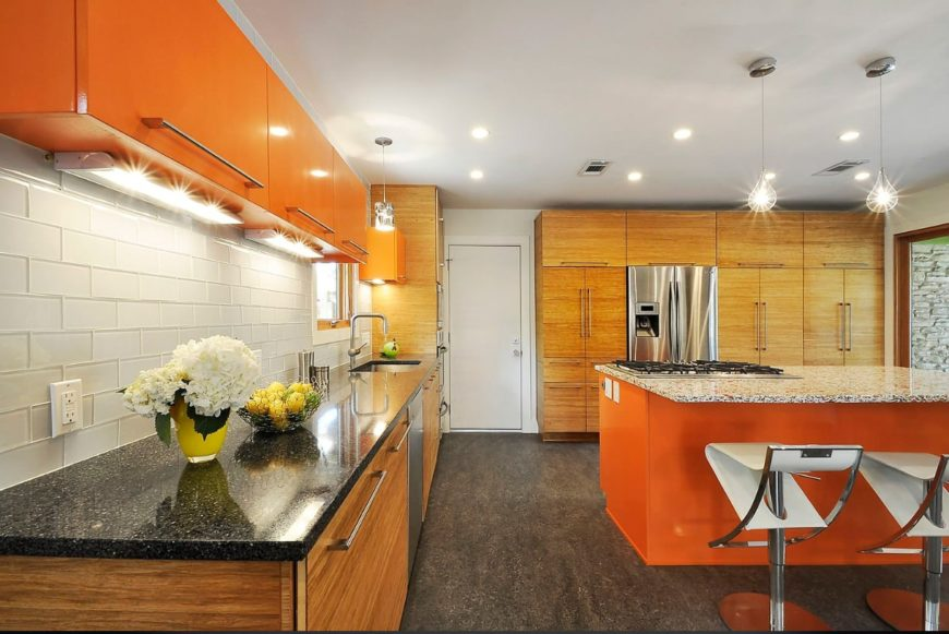 A dine-in kitchen with marble countertops, huge wooden cabinets, stainless steel appliances, and a combination of pendant and recessed lighting.