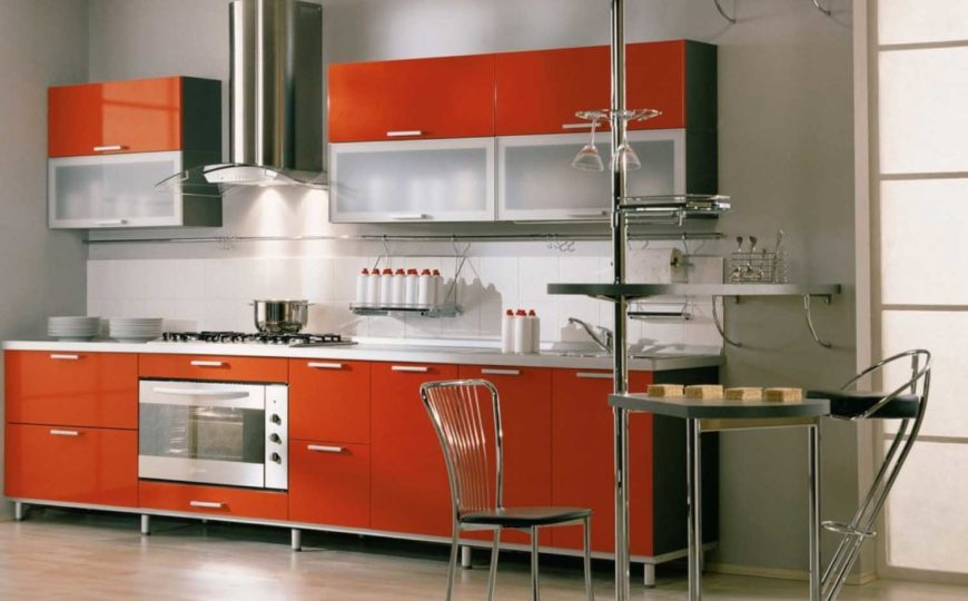 A single wall kitchen with stainless steel appliances and stainless steel accents, a hood, and burnt orange cabinets.