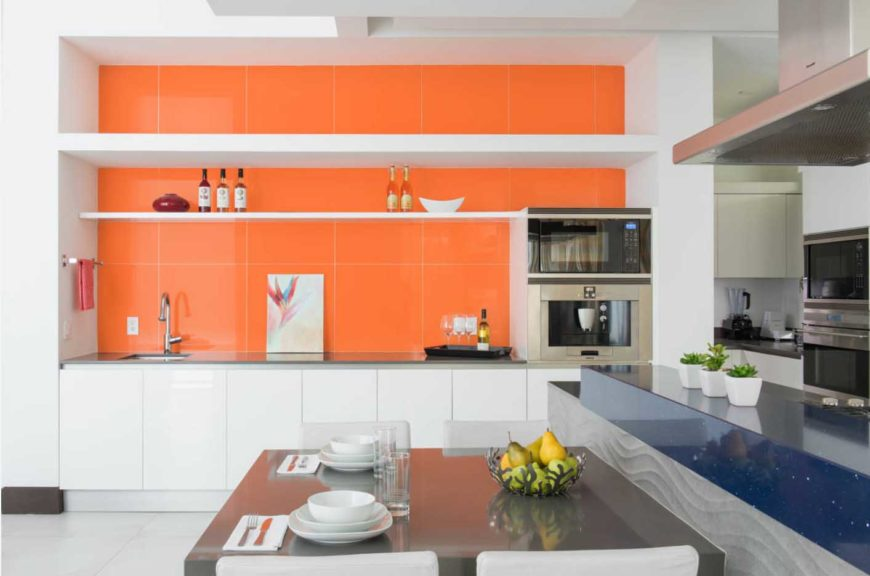 A dine-in kitchen with orange-tiled walls, stainless steel appliances, and white tiled floors.