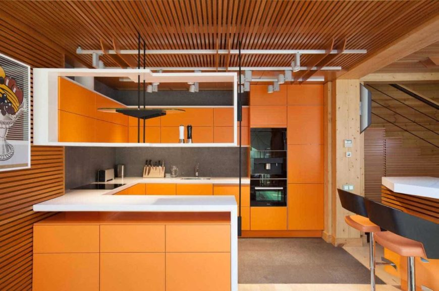 A G-shaped modern style kitchen with track lighting, black appliances, and orange cabinets.