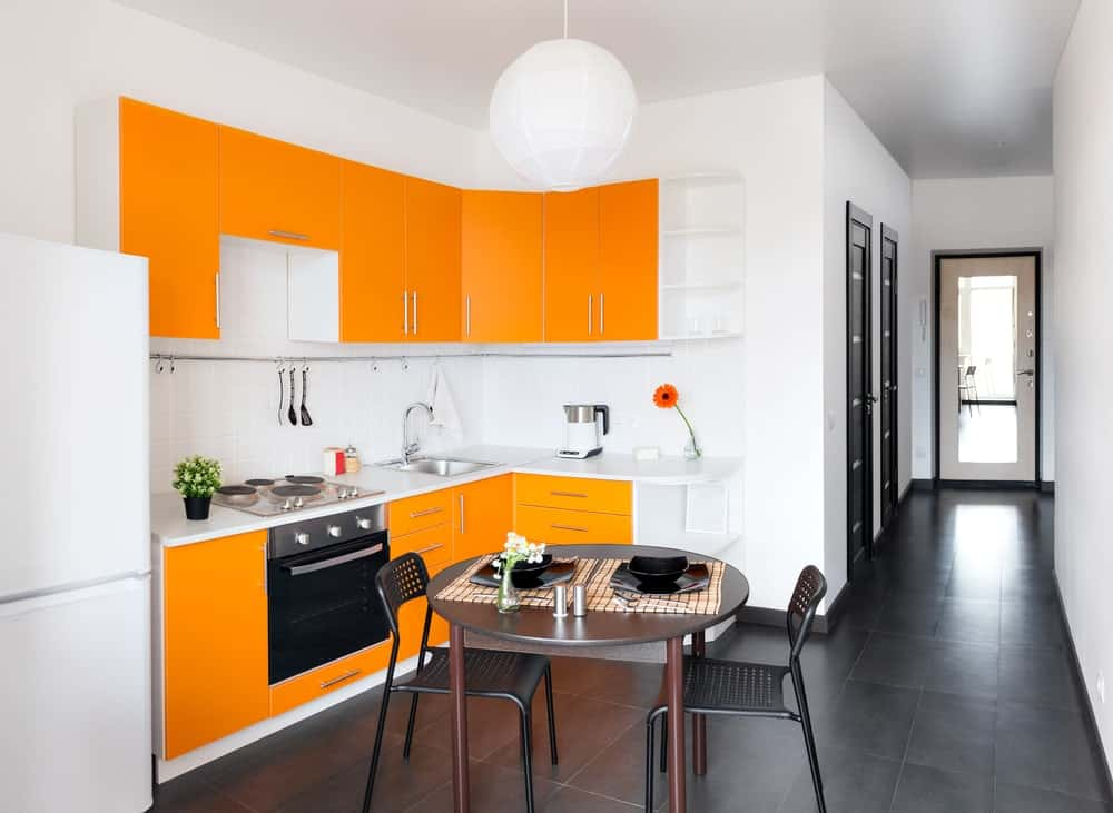 A small L-shaped kitchen accentuated with orange cabinets, a simple white pendant light, and a dine-in table for two which is perfect for couples.