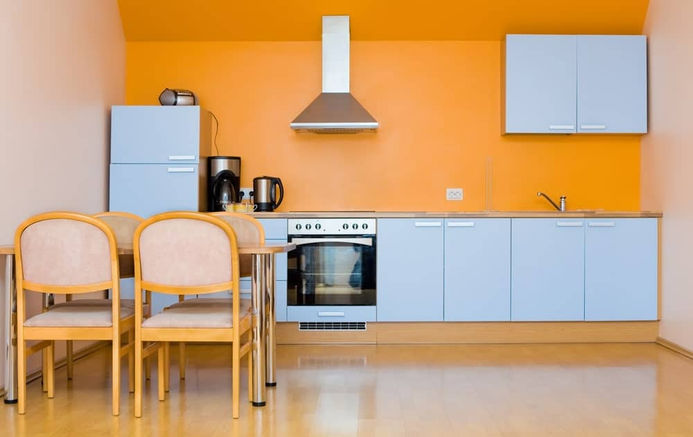 A minimalist wall kitchen with orange painted walls, stainless hood and appliances, and accents of light gray cabinets.