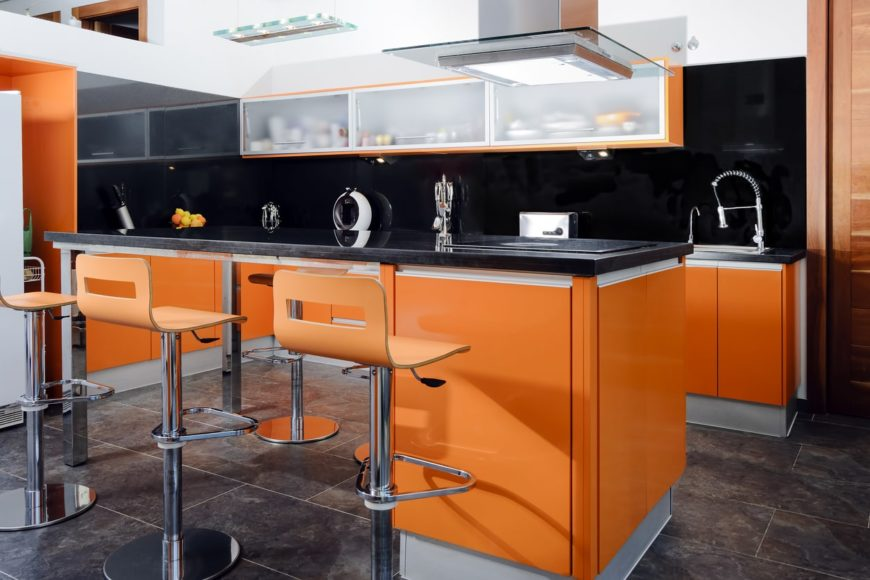 A modern style orange kitchen, with a sleek breakfast island, bar type stools, and tiled floors.