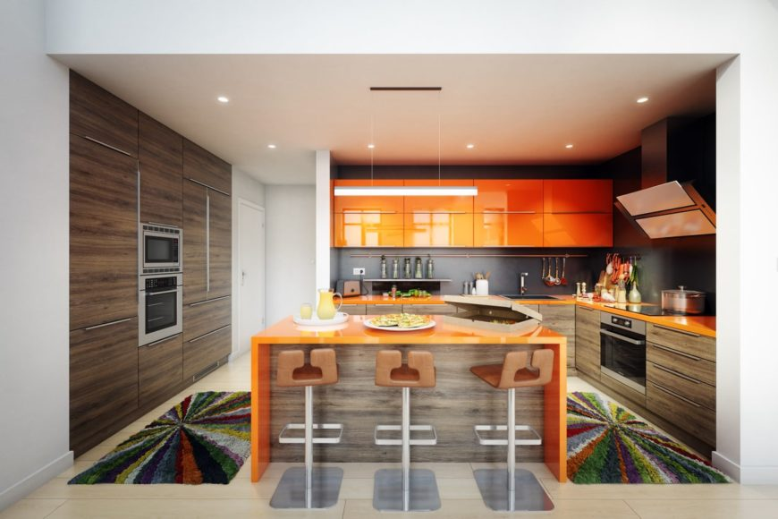An L-shaped kitchen with a breakfast island, bar type stools, a simple straight pendant light, shiny orange cabinets, and stainless steel appliances.