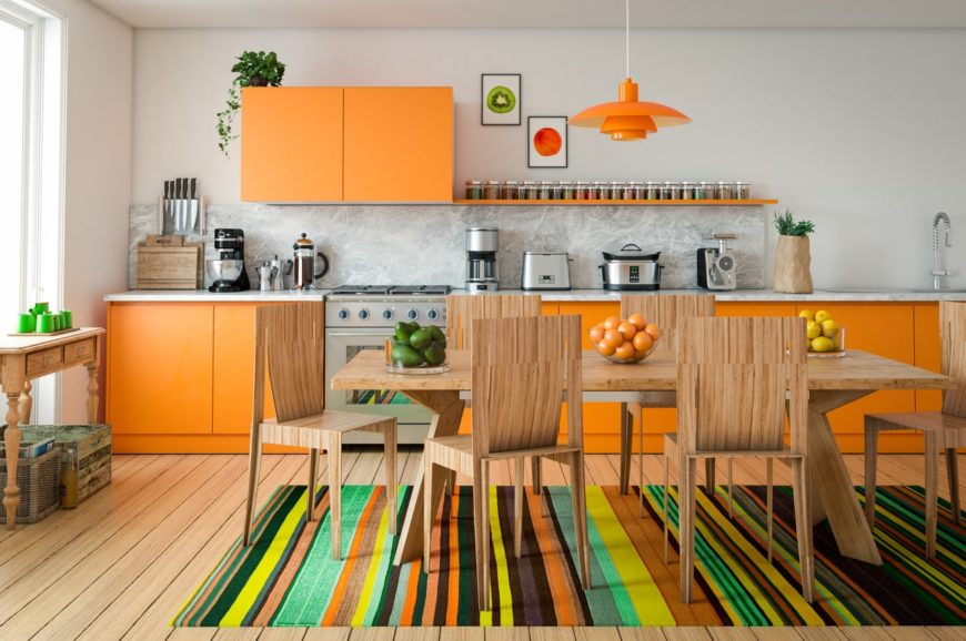 A playful wall kitchen with white walls, hardwood flooring, orange cabinets, stainless steel appliances, a simple orange pendant lighting, and a colorful striped rug.