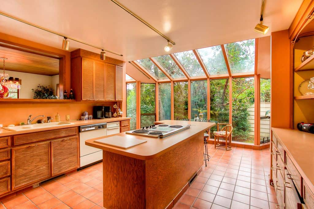 A rustic style kitchen with a glass-walled portion that allows a lot of sunshine, it has a wooden island, golden track lights, and an orange tiled floor.