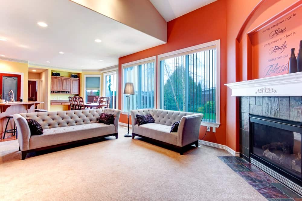 Vast carpeted living room with orange walls, two gray sofas, a fireplace, and large windows.