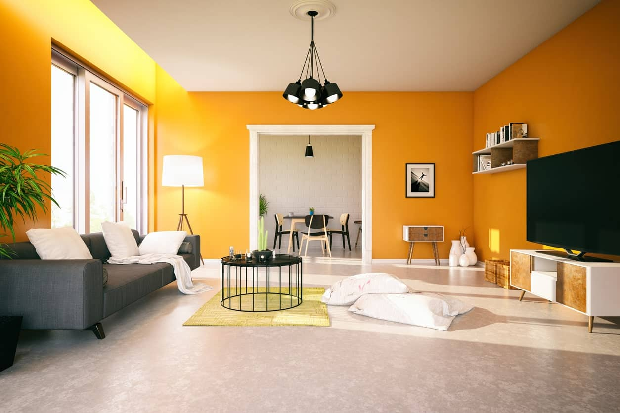 Vast living room with orange painted walls, floating shelves, gray sofa, round metal center table, and black pendant lighting.