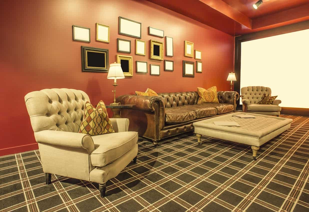 Elegant living room with two Mid-Century beige armchairs, brown leather Mid-century style sofa, checkered carpet flooring, orange walls, and a rectangular center table.