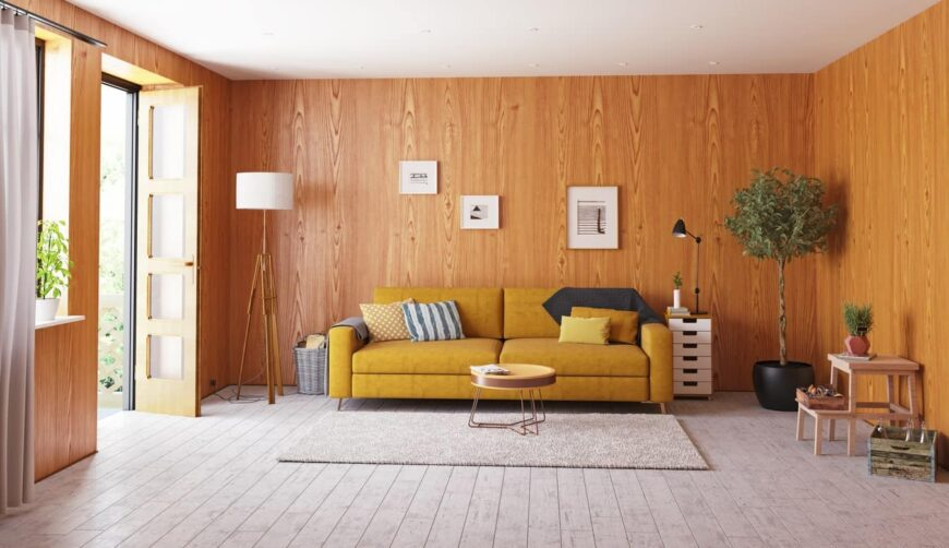 Simple Scandinavian living room with mustard yellow sofa, orangey hardwood walls, a floor lamp, and a stylish round Scandinavian center table.