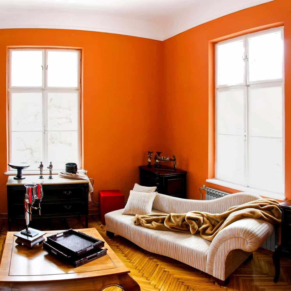 A warm burnt coral orange room with cozy chaise lounge, oriental corner cabinets, wood table and wooden floor with herringbone pattern.