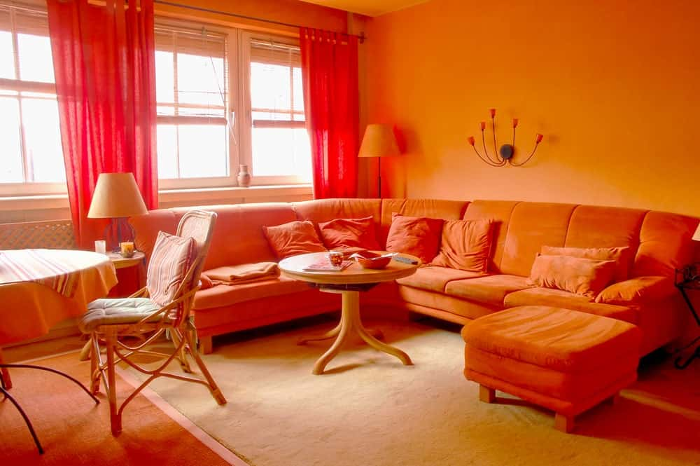 Living room with an explosion of orange from the sofa,the pillows, the round center table, the curtain, and the walls.