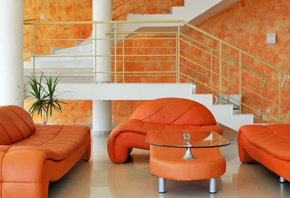 Modern living room with orange sofa, glass center table, and tiled floors.
