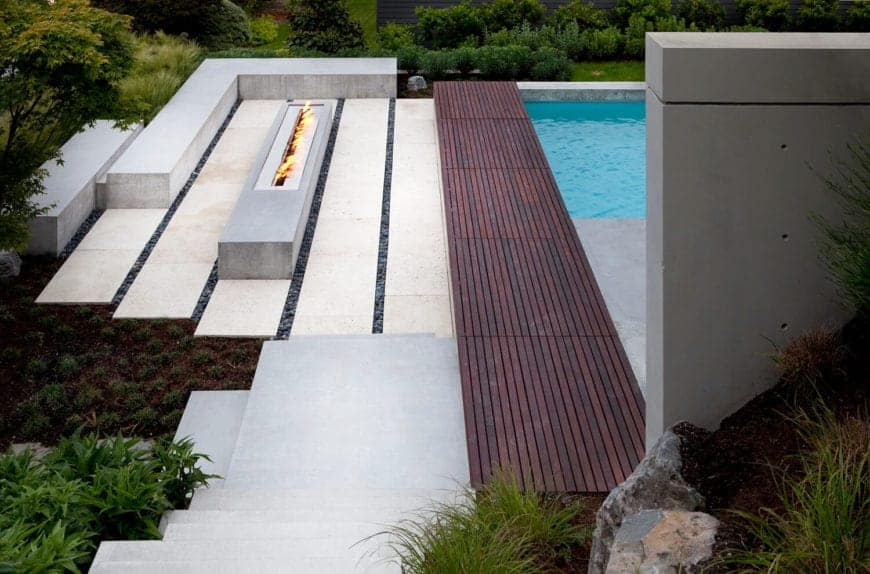 A closer look of the wood pool panel and a rectangular fire pit seated on a white concrete horizontal bars with a concrete L-shaped bench surrounded by ornamental grasses.